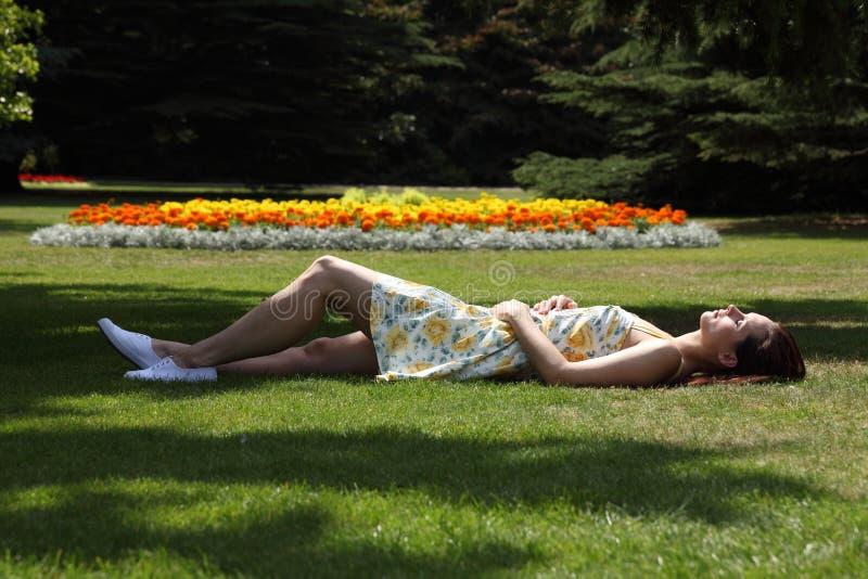 Mooie vrouwenslaap in de zon van de tuinzomer royalty-vrije stock foto's