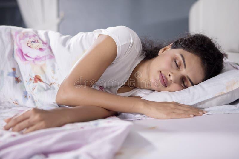 Mooie vrouwenslaap goed op het bed stock afbeelding