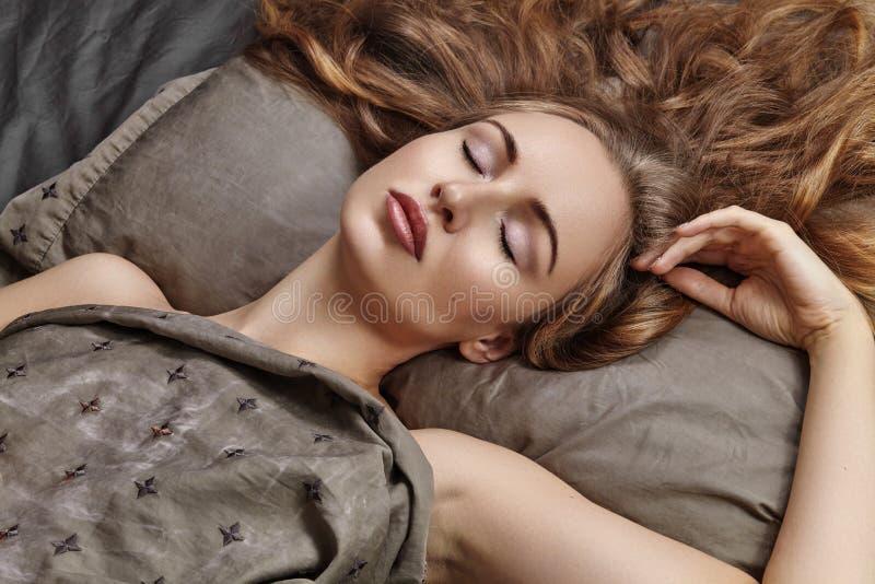 Mooie Vrouwenslaap terwijl het liggen in Bed met Comfort Zoete Dromen Sexy model met het krullende haar ontspannen op bladen stock foto's