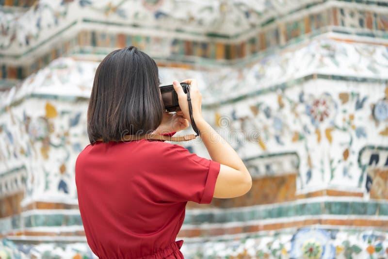 Mooie vrouwentoerist Gehouden camera om het geheugen te vangen Wat Arun-tempel in Thailand het gebruiken als achtergrondreisconce royalty-vrije stock afbeeldingen