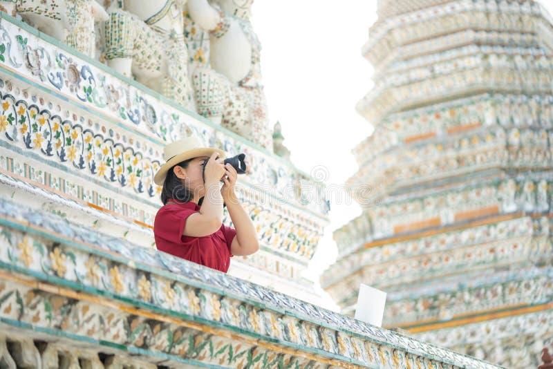 Mooie vrouwentoerist Gehouden camera om het geheugen te vangen Wat Arun-tempel in Thailand het gebruiken als achtergrondreisconce stock foto