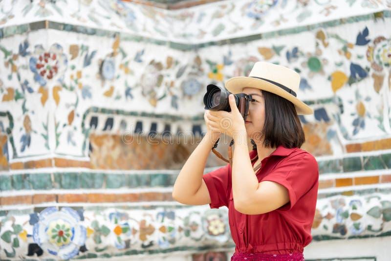Mooie vrouwentoerist Gehouden camera om het geheugen te vangen Wat Arun-tempel in Thailand het gebruiken als achtergrondreisconce stock afbeelding