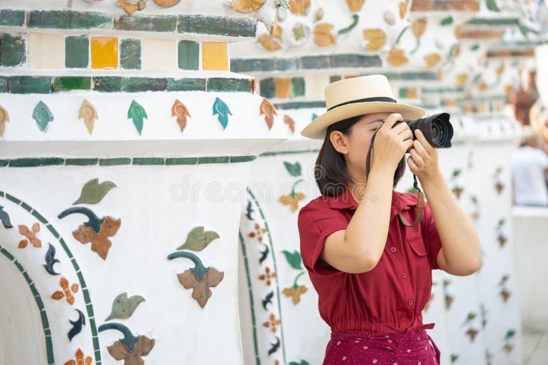 Mooie vrouwentoerist Gehouden camera om het geheugen te vangen Wat Arun-tempel in Thailand het gebruiken als achtergrondreisconce stock foto's