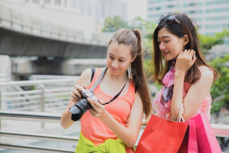 Mooie vrouwentoeristen die foto in haar camera na trave kijken royalty-vrije stock afbeelding