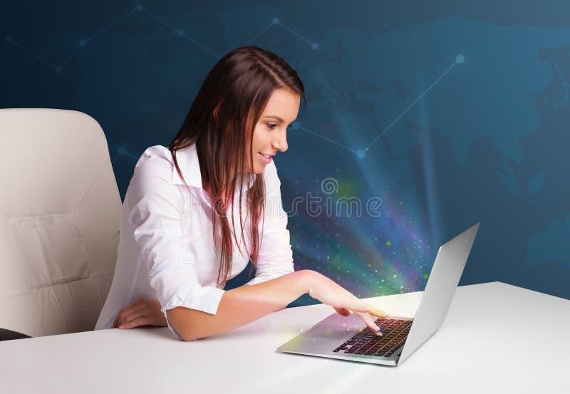 Mooie vrouwenzitting bij bureau en het typen op laptop met abstra stock afbeelding