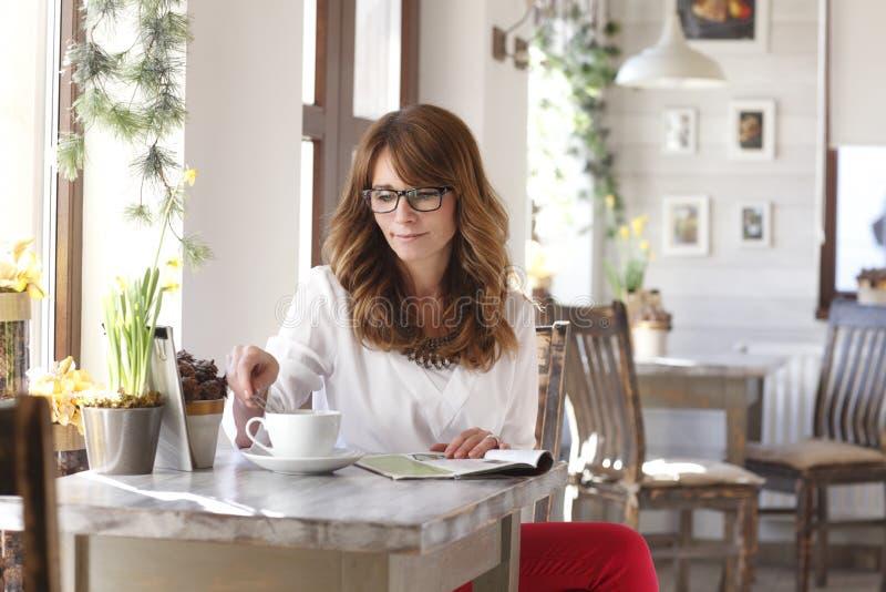 Mooie vrouwenzitting bij bureau in koffiewinkel stock fotografie