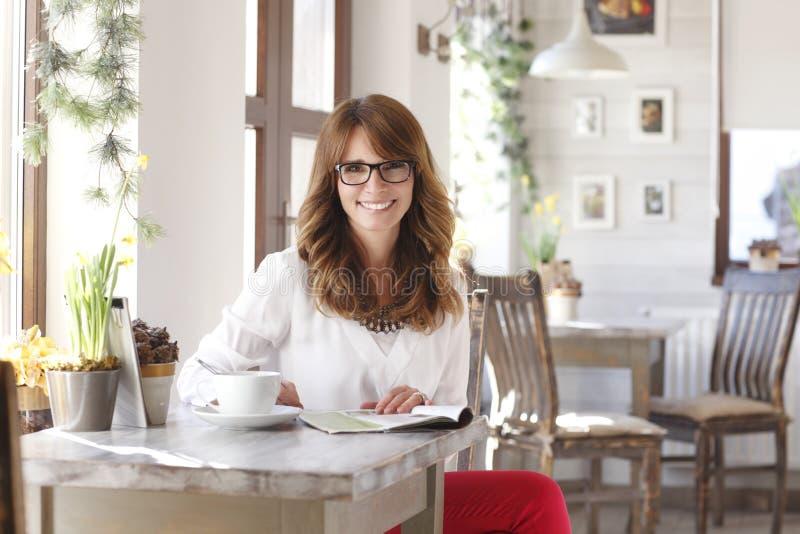 Mooie vrouwenzitting bij bureau in koffiewinkel stock afbeelding