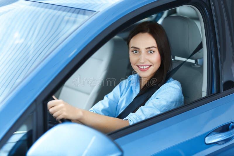 Mooie vrouwenzitting in een auto stock afbeelding