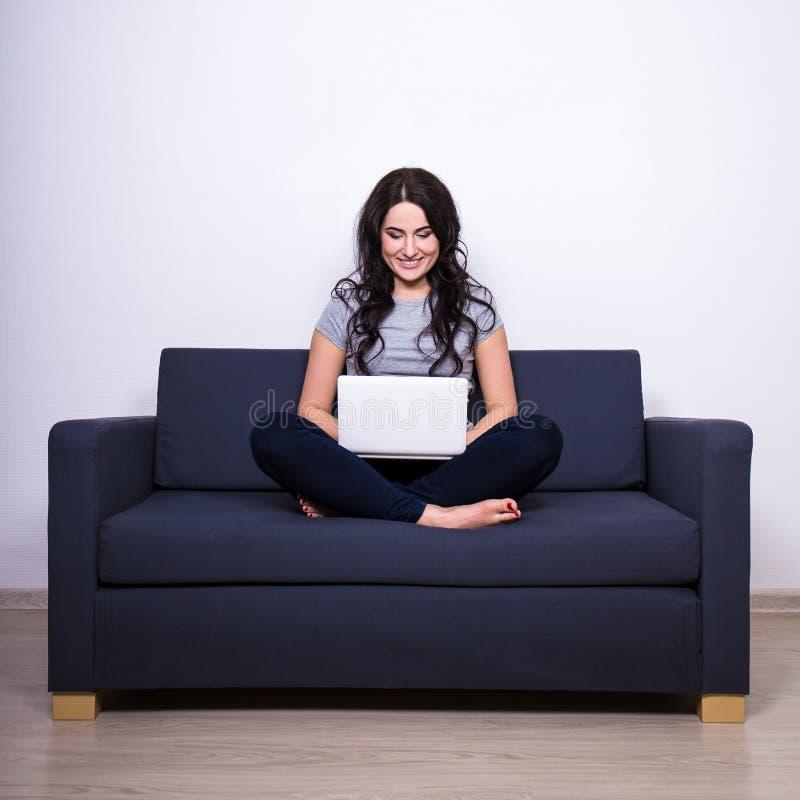 Mooie vrouwenzitting op bank en thuis het gebruiken van laptop stock foto