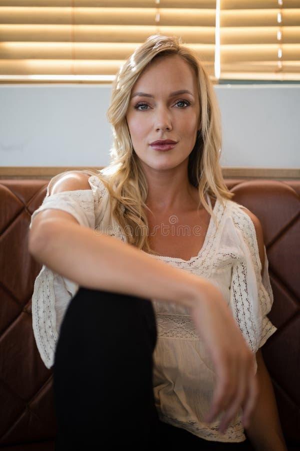 Mooie vrouwenzitting op bank in restaurant royalty-vrije stock foto's