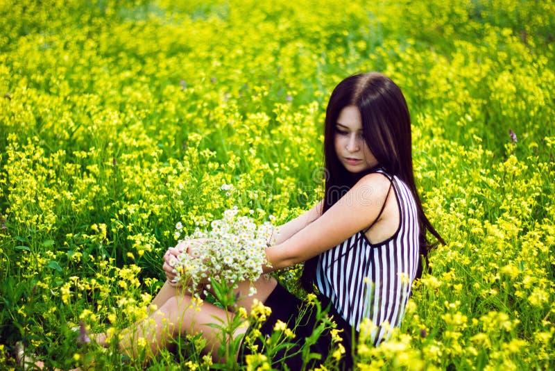 Mooie vrouwenzitting op de gele achtergrond van het bloemgebied royalty-vrije stock afbeeldingen