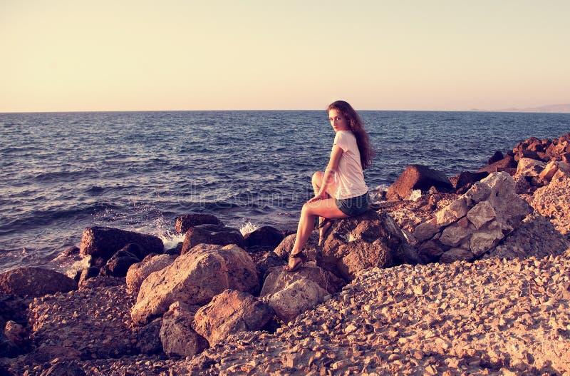 Mooie vrouwenzitting op de rots dichtbij blauwe overzeese en hemelwi stock afbeelding
