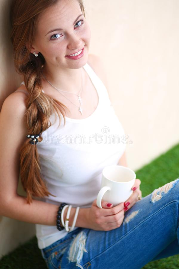 Download Mooie Vrouwenzitting Op De Vloer En Holding Een Kop Mooie Vrouw Stock Foto - Afbeelding bestaande uit thee, koffie: 107702594