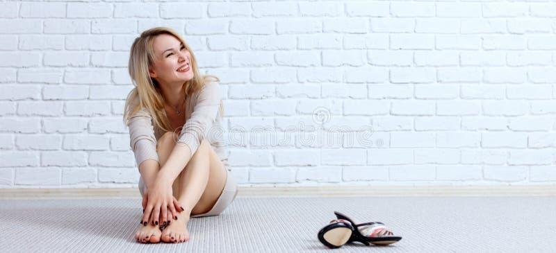 Mooie vrouwenzitting op de vloer over bakstenen muurachtergrond royalty-vrije stock fotografie