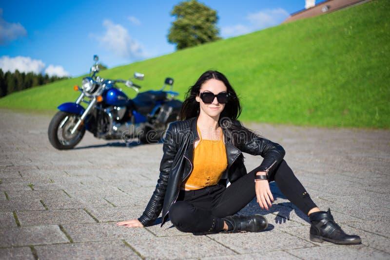 Mooie vrouwenzitting op de weg met retro motor stock foto's