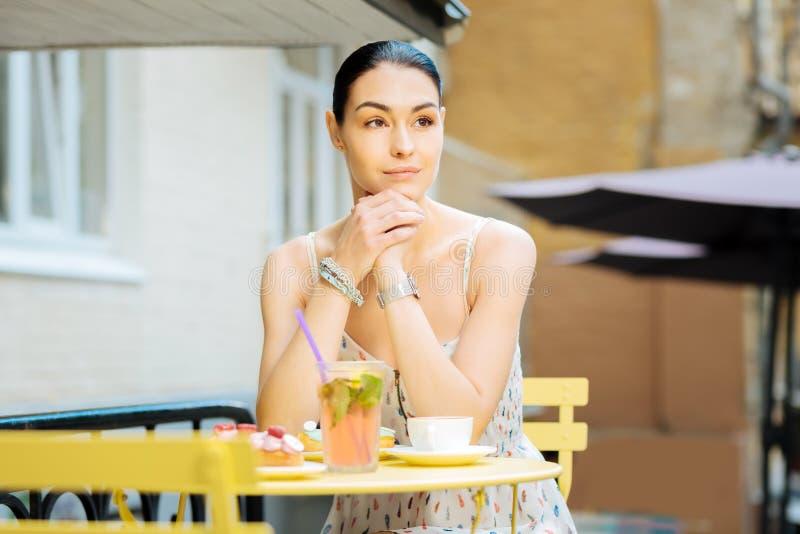 Mooie vrouwenzitting op een koffieterras en wachten voor een vriend stock foto's