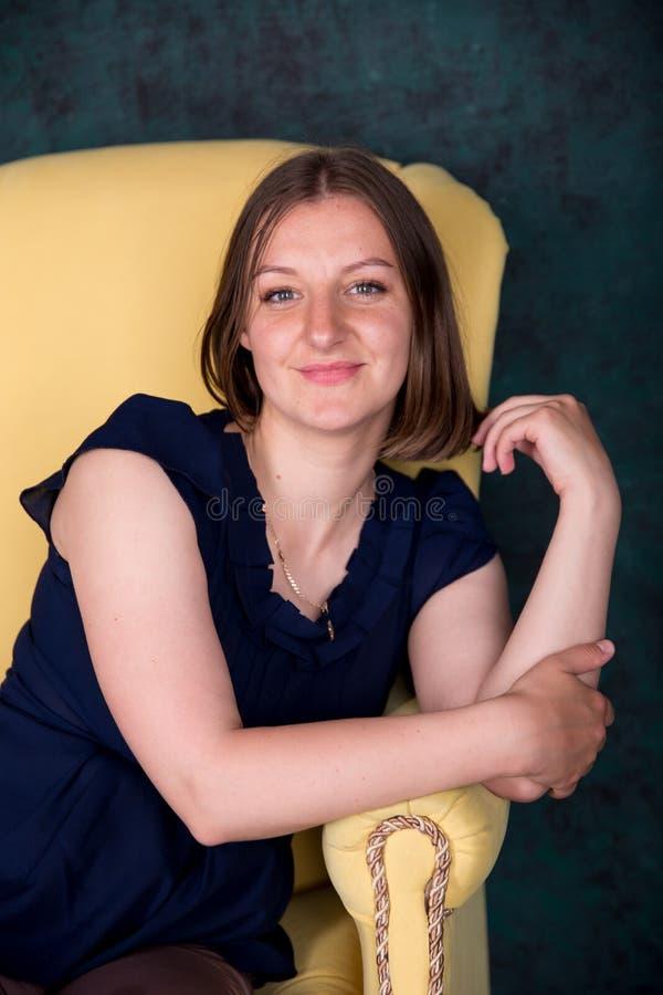 Mooie Vrouwenzitting op Grote Leunstoel in Studio royalty-vrije stock afbeelding