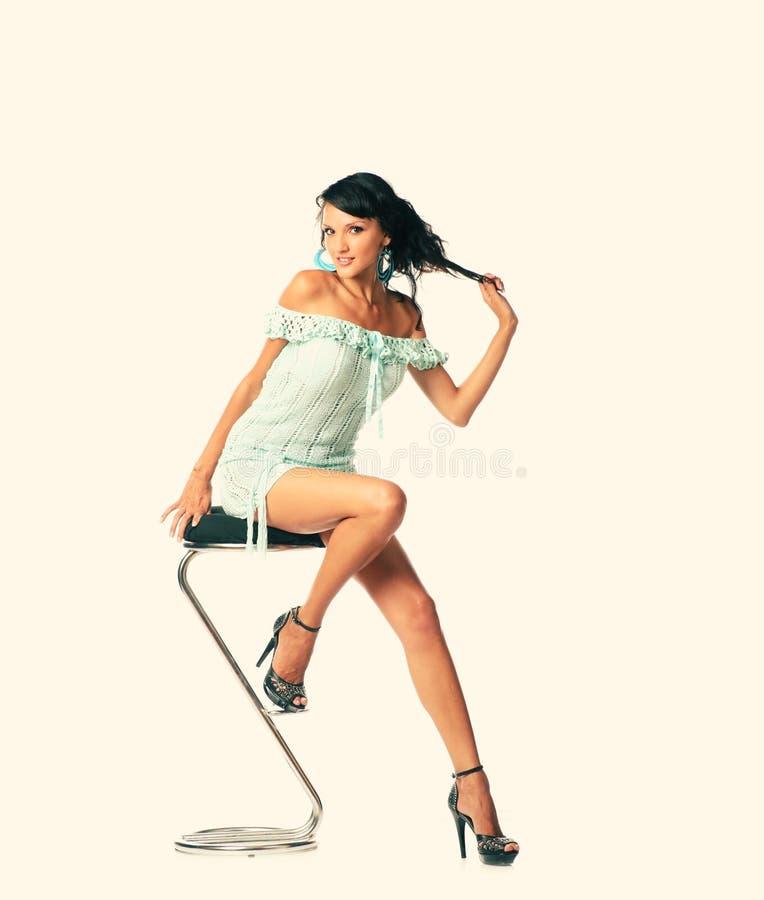 Mooie vrouwenzitting op stoel Volledig lichaam dat in manierstijl wordt geschoten royalty-vrije stock fotografie