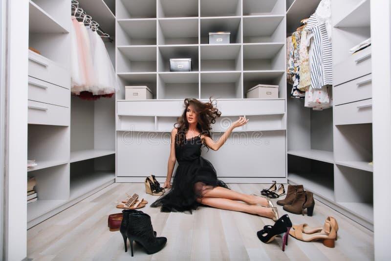 Mooie vrouwenzitting op vloer in modieuze garderobe royalty-vrije stock afbeelding