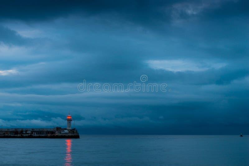 Mooie vuurtoren op de kust bij schemer, regenachtige wolken over stock foto