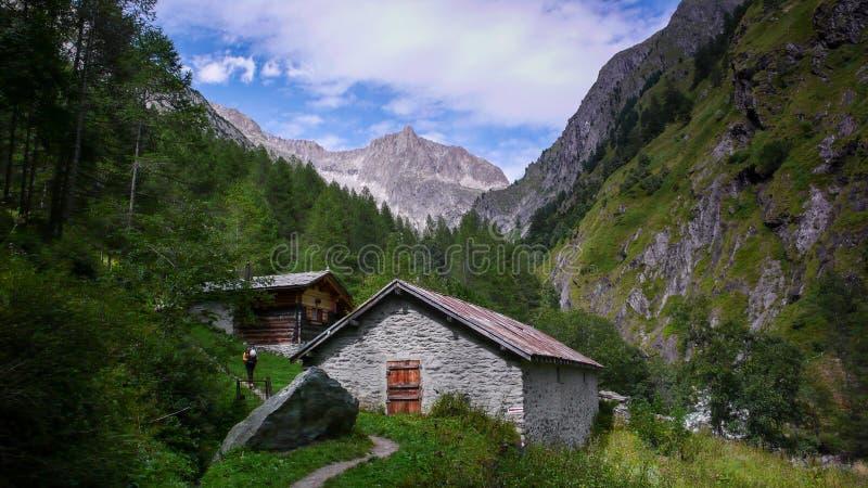 Mooie weelderige bergvallei met oude erachter plattelandshuisjes en hoge alpiene pieken royalty-vrije stock afbeeldingen