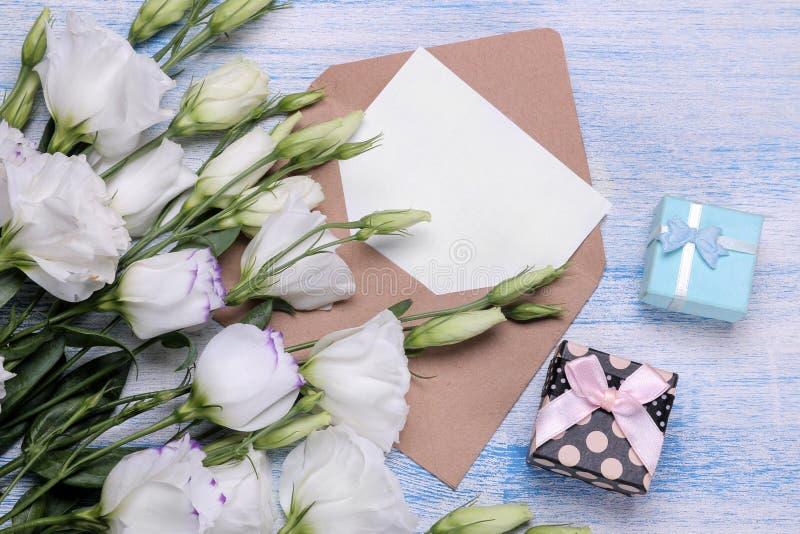 Mooie witte bloemen Eustomaboeket met giften, een envelop en een spatie voor tekst op een blauwe houten lijst Mening van hierbove royalty-vrije stock foto