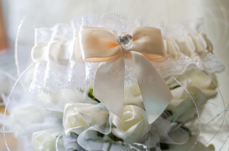 Mooie witte bruid` s kouseband met bloemen stock afbeelding