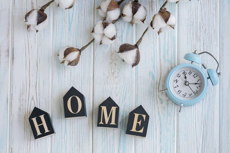 Mooie witte katoenen bloemen, kubussen met brieven en blauwe wekker op turkooise houten flatlay achtergrond, stock afbeelding