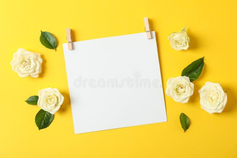 Mooie witte rozen en leeg blad op gele achtergrond stock afbeelding