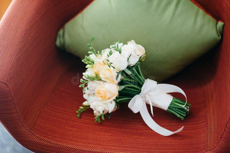 Mooie witte rozen met lint op rode leunstoel met hoofdkussen Het concept van het huwelijk Bloemen Het concept van de viering Brui stock foto