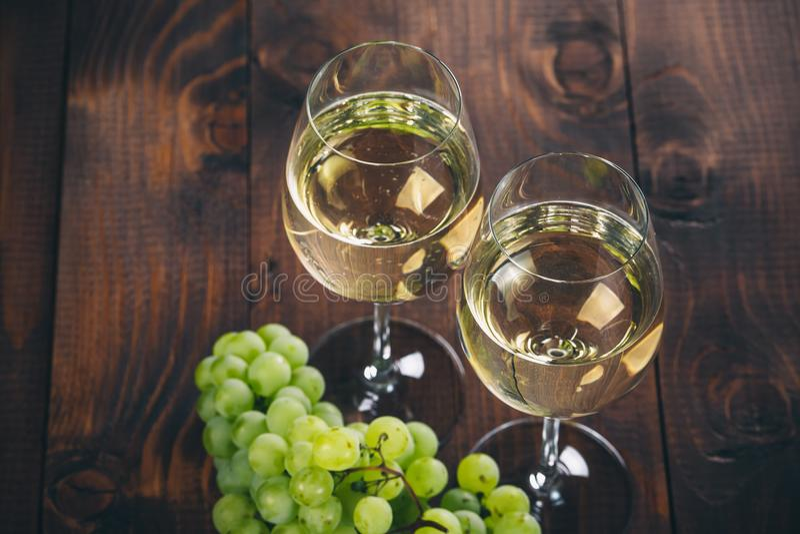 Mooie Witte wijn in wijnglas met een bos van groene druiven, op een houten achtergrond met vrije ruimte royalty-vrije stock foto