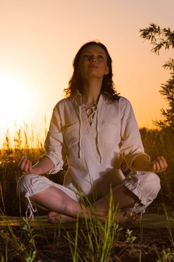 Mooie Yogavrouw die tegen zonsopgang situeren stock foto's