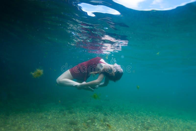 Mooie yogi die met een rood dier dansen onderwater royalty-vrije stock fotografie