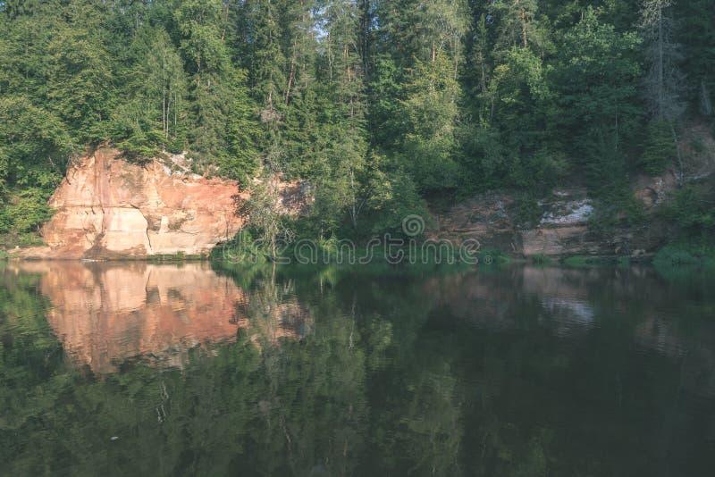 mooie zandsteenklippen op de kusten van rivier Amata in Letland - de uitstekende retro film ziet eruit stock afbeeldingen