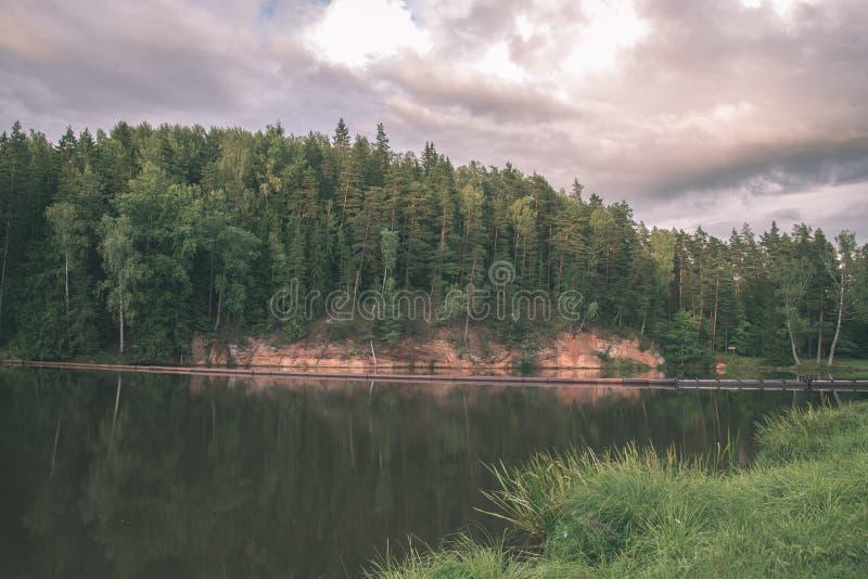 mooie zandsteenklippen op de kusten van rivier Amata in Letland - de uitstekende retro film ziet eruit stock foto