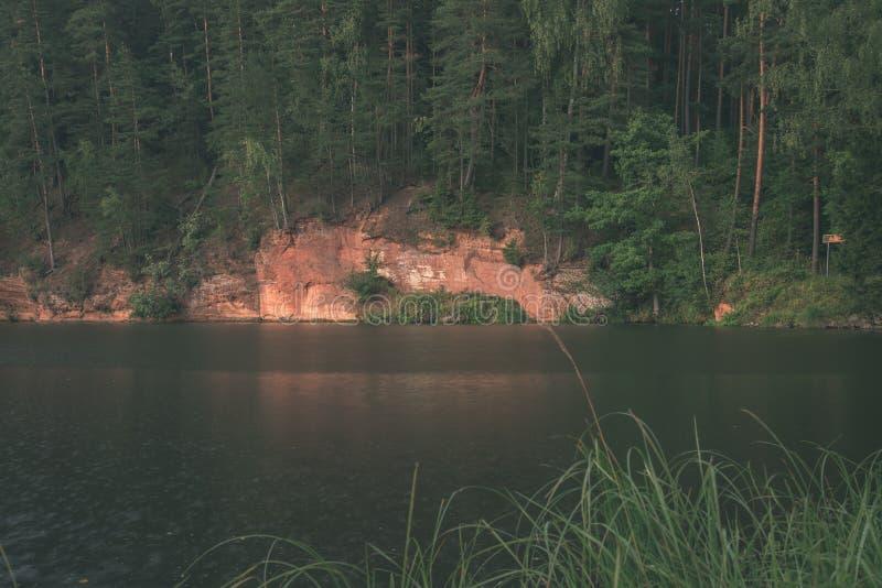 mooie zandsteenklippen op de kusten van rivier Amata in Letland - de uitstekende retro film ziet eruit royalty-vrije stock afbeelding