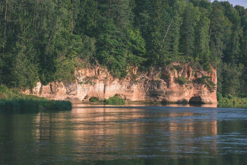 mooie zandsteenklippen op de kusten van rivier Amata in Letland - de uitstekende retro film ziet eruit stock fotografie