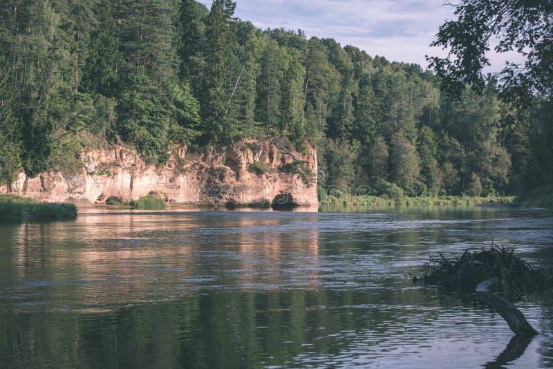 mooie zandsteenklippen op de kusten van rivier Amata in Letland - de uitstekende retro film ziet eruit stock afbeelding