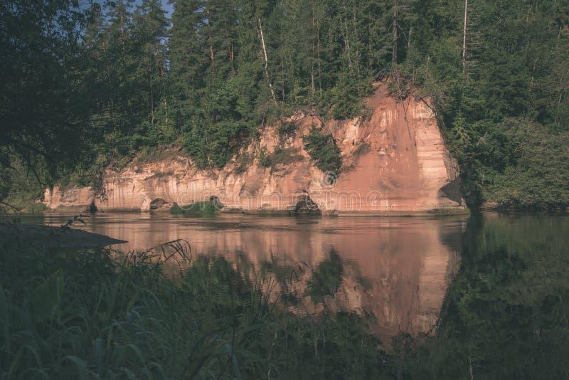 mooie zandsteenklippen op de kusten van rivier Amata in Letland - de uitstekende retro film ziet eruit stock foto's