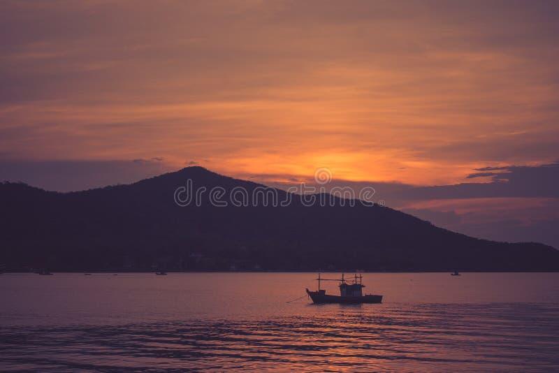 Mooie zeegezichtmening van vissersboot die op het overzees met zonsonderganglicht op de achtergrond in schemeringtijd drijven royalty-vrije stock foto
