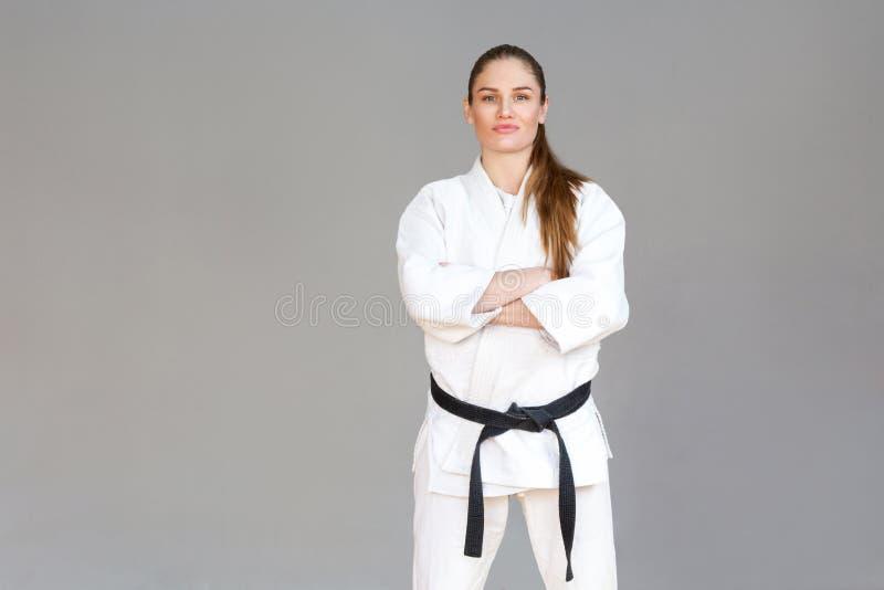 Mooie zekere atletische jonge vrouw in witte kimono en bla stock afbeeldingen