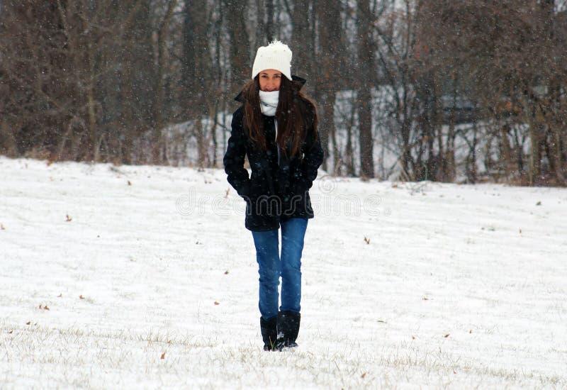Mooie zekere groene ogentiener die onder sneeuw lopen terwijl het sneeuwen stock foto