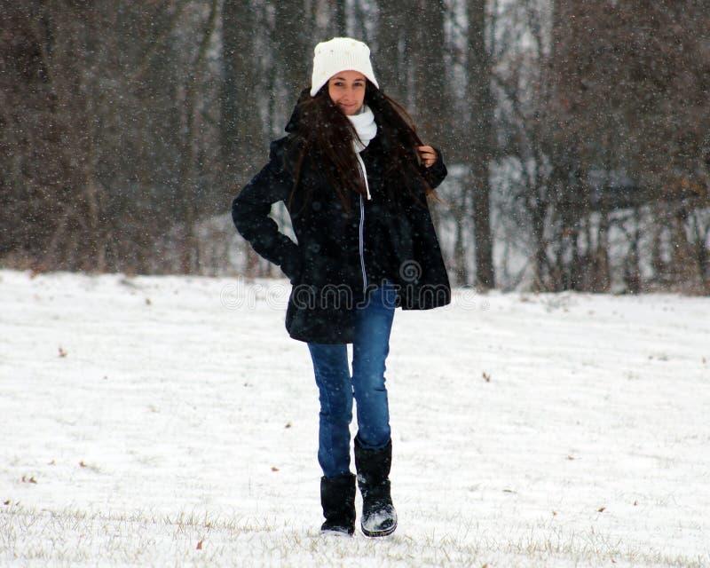 Mooie zekere groene ogentiener die onder sneeuw lopen terwijl het sneeuwen stock foto's