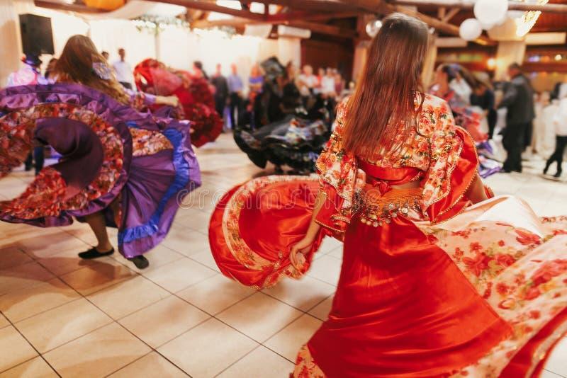 Mooie zigeunermeisjes die in traditionele rode bloemenkleding bij huwelijksontvangst dansen in restaurant Vrouw die zigeunertaald stock foto