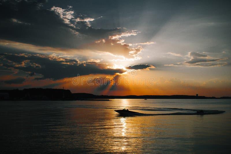 Mooie zon achter de wolken, het overzees en de boot stock afbeeldingen