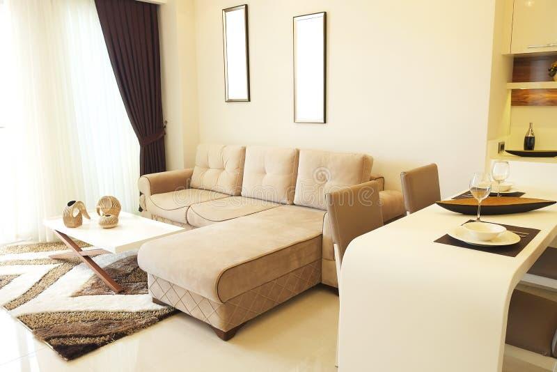 Mooie zon zijflat met eenvoudig minimalistic modern binnenlands ontwerp, de open woonkamer van de plankeuken in zonlicht stock fotografie