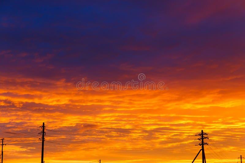 Mooie Zonsondergang Antennes en pijpen bij zonsondergang Gelaagde regenwolken Heldere blauwe oranje achtergrond De textuur van de stock foto