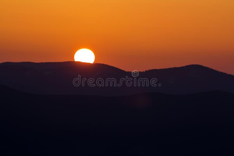 Mooie zonsondergang in bergen Brede panoramamening van grote heldere witte zon in dramatische oranje hemel over donkere bergketen stock fotografie