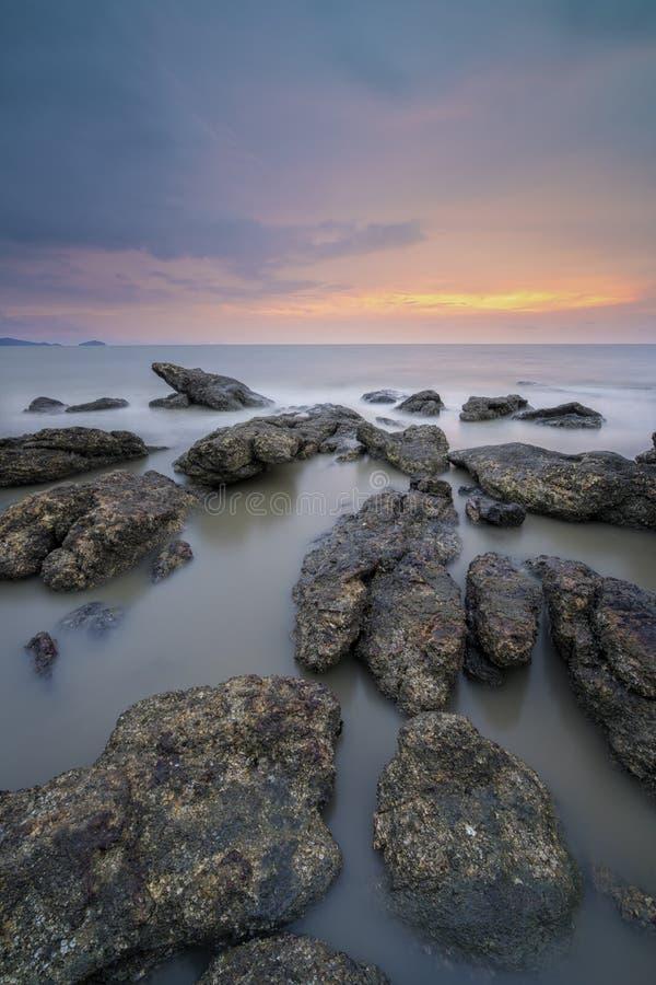 Mooie zonsondergang bij rotsachtig strand stock foto