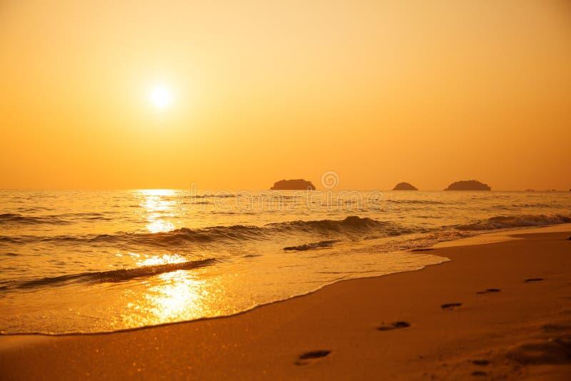 Mooie zonsondergang boven het overzees Voetafdrukken in het zand royalty-vrije stock afbeeldingen